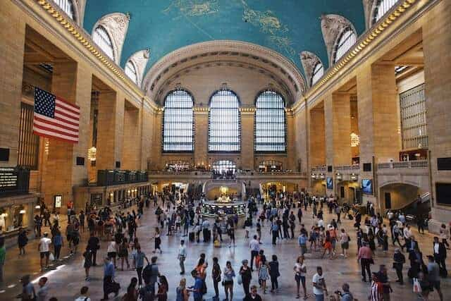 Grand Central Terminal Building with domed roof, shiny concrete floor covered in people moving through