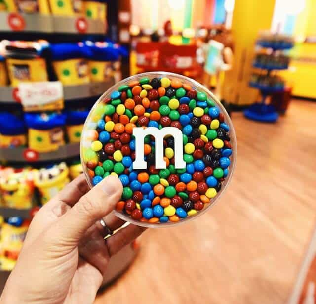 Hand holding a round clear plastic tub filled with multicoloured M&Ms in the M&Ms shop