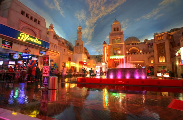 Miracle Mile row of shops indoor under a painted blue sky with white clouds, a waterfall lit up to the right