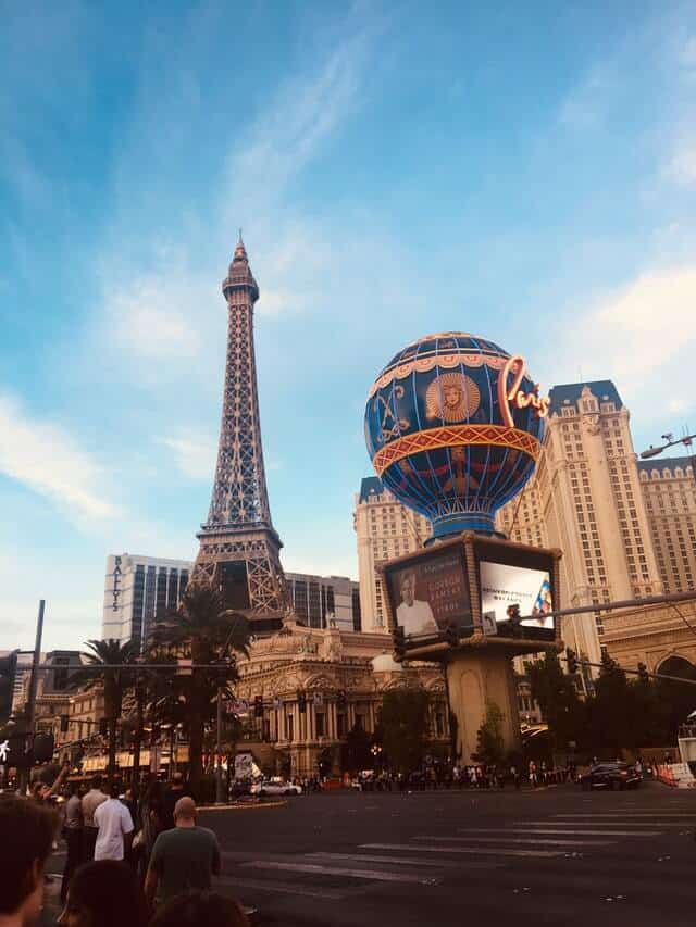 Paris Hotel & Casino, the replica Eiffel Tower in the background and the blue hot air balloon in the foreground bearing the word 'Paris'
