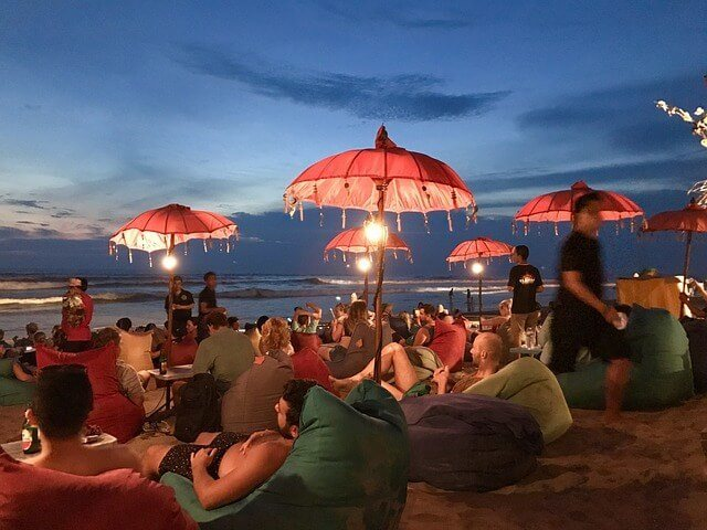 People sat on beanbags on the beach at dusk underneath gypsy umberellas lit by fairy lights