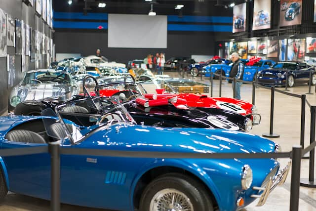 Vintage cars parked up in an indoor display, roped off to visitors at the Shelby American Heritage Center