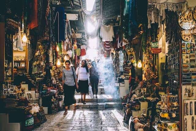 A woman walking towards the camera flanked either side by stalls and shops inside the Medina in Jerusalem