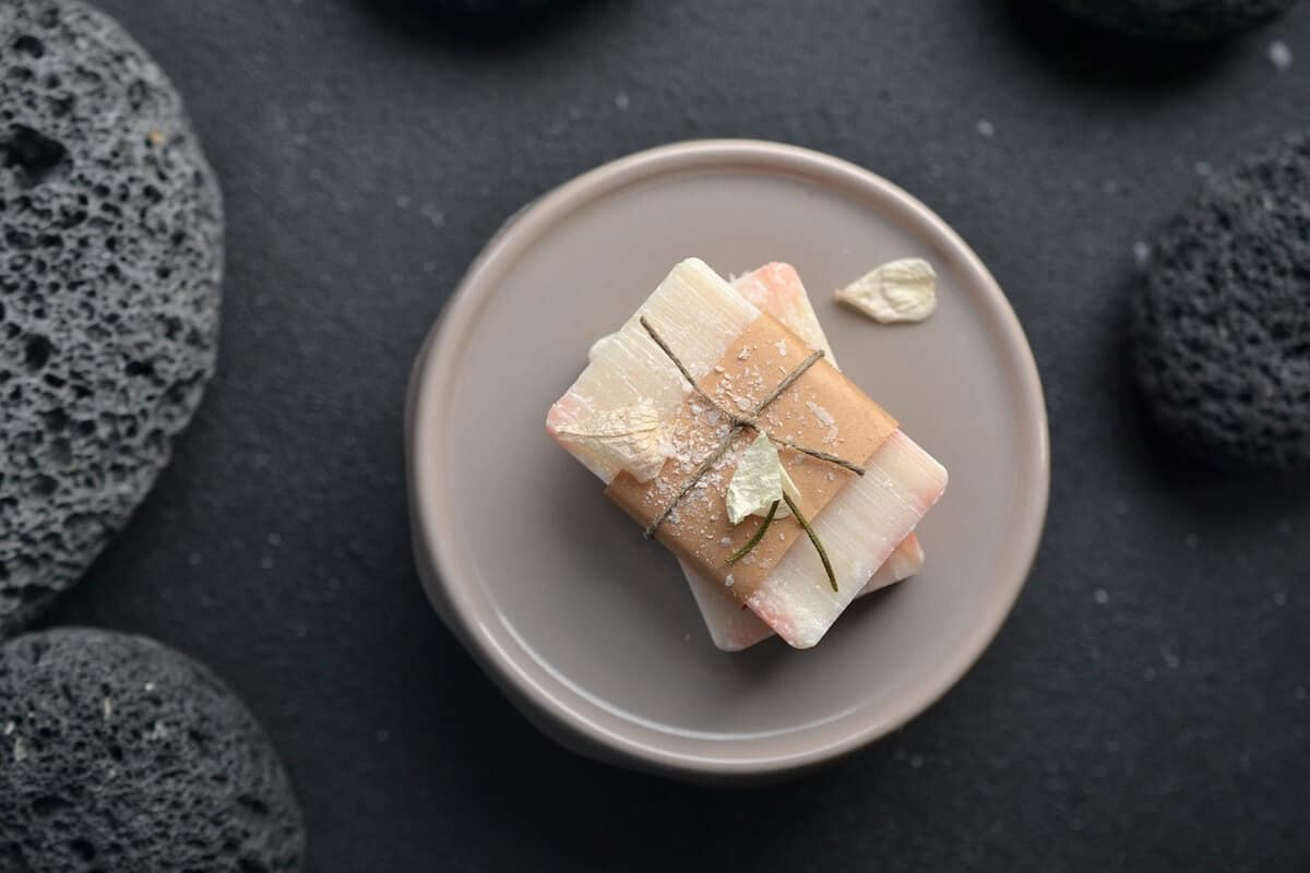 Solid Travel Toiletries Cover Photo of Bar of soap wrapped in paper on a rose pink plate on a black table