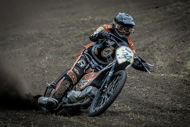 Man riding a speedway bike around the dirt track