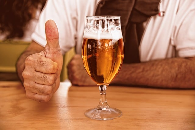 Glass of beer in front of a man with a white shirt with his thumb up