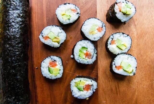 Full Hosomaki Sushi roll on the left with sliced sushi roll pieces laid out on a wooden board to the right