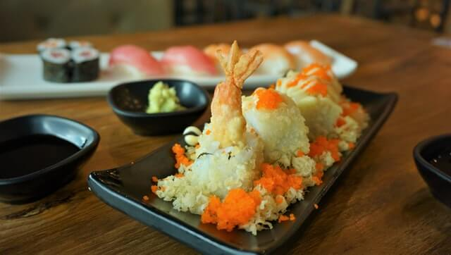 Shrimp Tempura Sushi Roll on a plate with other types of sushi behind it along with a pout of wasabi