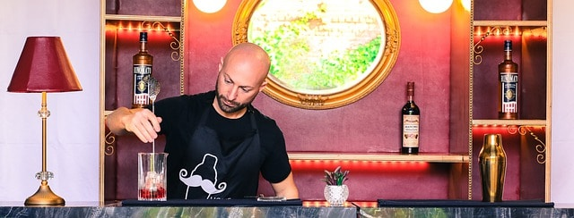 Bald Bartender wearing black shirt with cocktail shaer motif stiring a cocktail on the bar in front of him