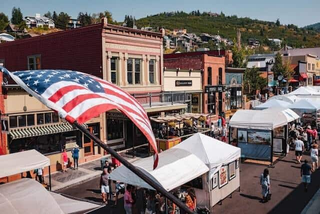 Aerial view of Park Citys Main Street featuring an aerial view of main street in Park City in summer with an American flag in the foreground and white tents of the market lining the street
