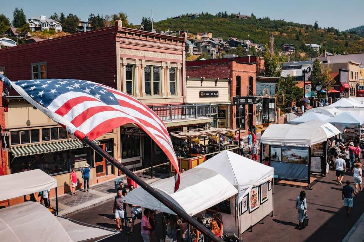 Cover photo from Things to do in Park City Utah featuring an aerial view of main street in Park City in summer with an American flag in the foreground and white tents of the market lining the street