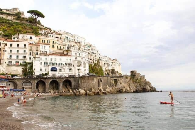 View from standing at the beach looking up to the houses on the cliff in Amalfi Italy