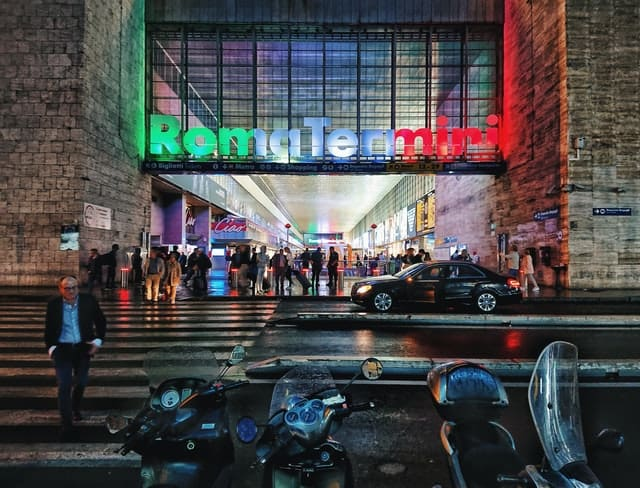 Facade of Roma Termini (Rome Train Station) bathed in a strip of green, white and red light (the colours of the Italian Flag)