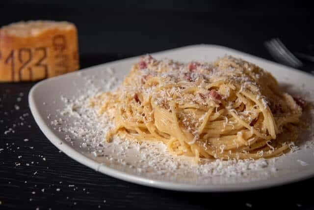 Spaghetti Carbonara on a white plate covered in parmesan cheese on a black table cloth in Rome
