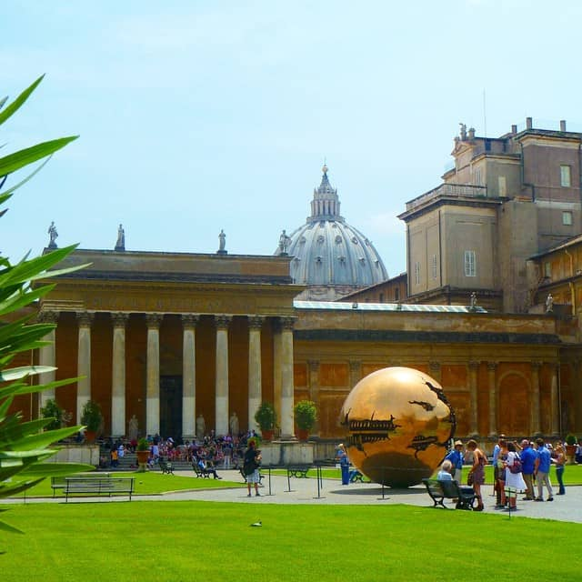 The gardens inside the Vatican Museum with green grass, golden globe and st Peters Bascilica in the background