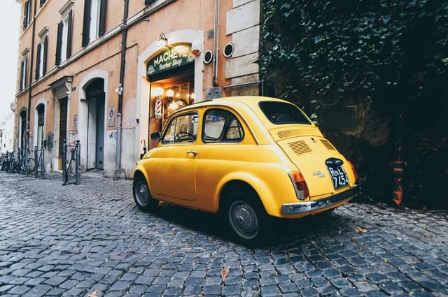 Yellow Fiat 500 parked on a cobbled street next to a restaurant in Rome