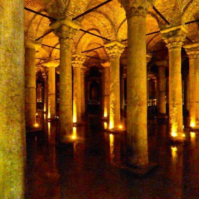 Columns equidistent apart in a grid formation supporting domed roof sections sitting in a body of water, with each column is uplit by a spotlight