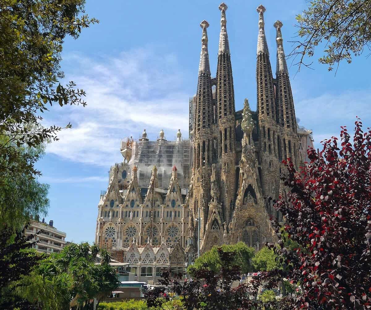 Best Places to Visit in Barcelona header image of the Sagrada Familia framed by tress from the park opposite and backed by a blue sky