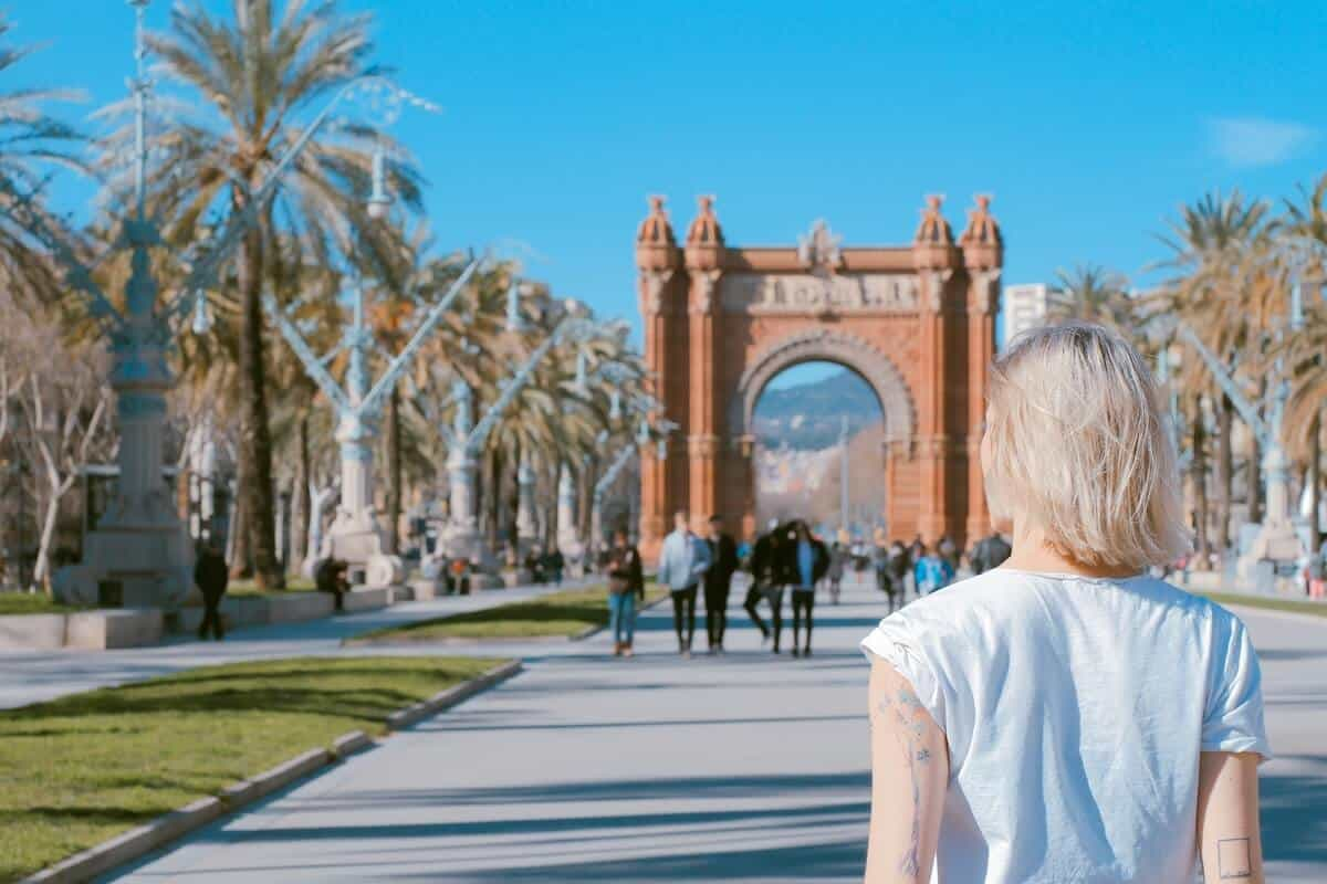 Barcelonas Red Moorish Style Arc de Triomf at the end of a grey concrete pathway through a park; in the forground a woman with blond hair and a blue shirt has her back towards the camera looking towards it. This is the header image for the Best Places to Visit in Barcelona