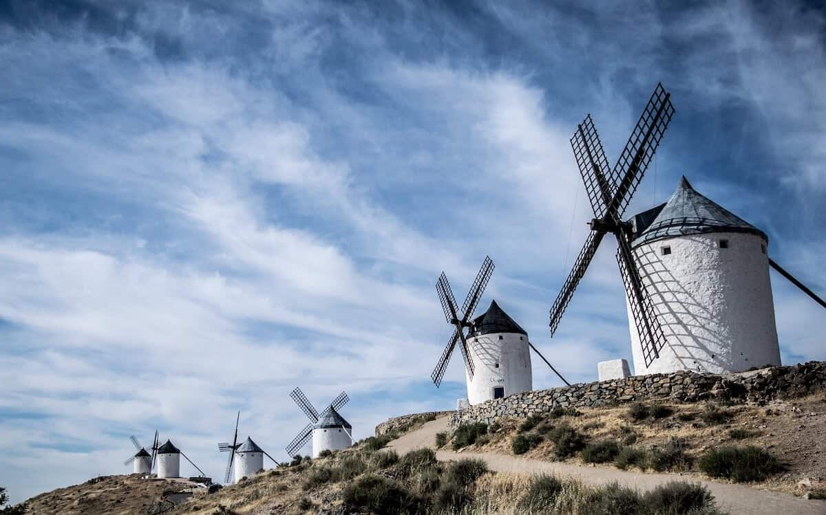 Best Places to Visit in Spain Header Image of the White windmills on top of the hill at Consuegra, Spain