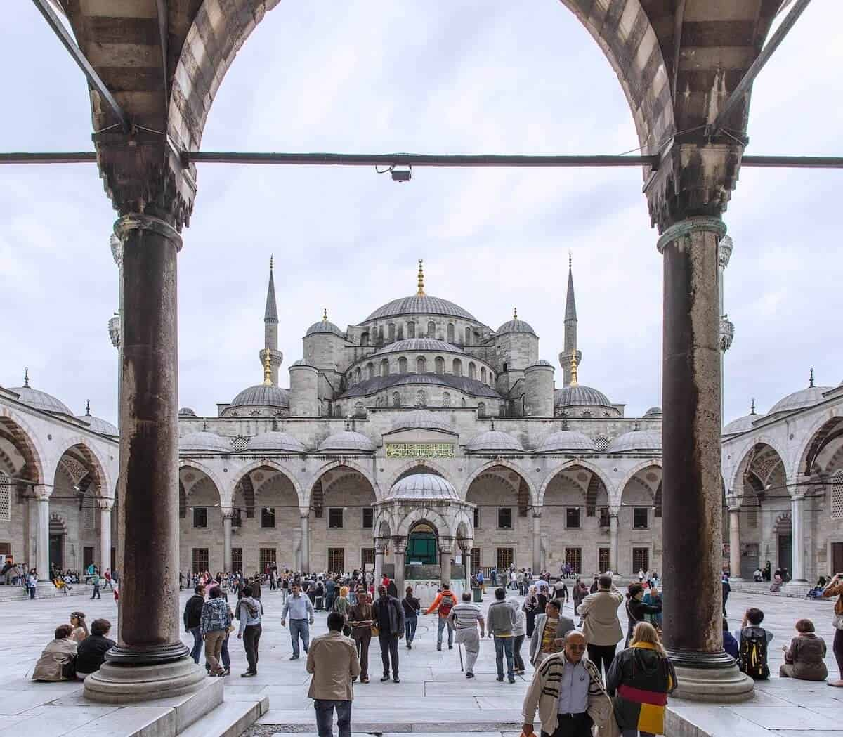 The view from inside the Blue Mosque feauring a courtyard surrounded by arched columns looking up towards the blue multi-domed structure of the mosque eith 2 of the minarets stading tall either side. Taking in this view is one fo the Best Things to do in Istanbul Turkey