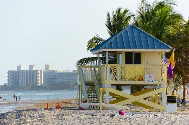 Large yellow elevated wooden hut on the beach with palm trees behind it in Biscane Bay Florida