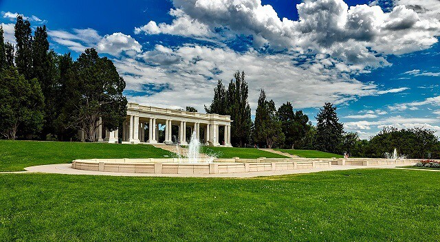 White Columade greco-roman style structure surrounded stands behind a simple fountain surrounded by green grass and under a bright blue sky 90% covered in light white clouds in Cheesman Park Colorado
