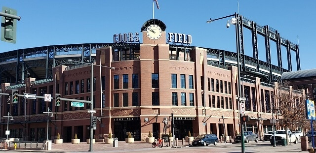 Cured facade of Coors Field Stadium with Coor and Field spelled out either side of a giant clock on top of the building under a clear blue sky