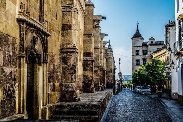 Gothic style buildings lining a cobblestone street in Cordoba Spain