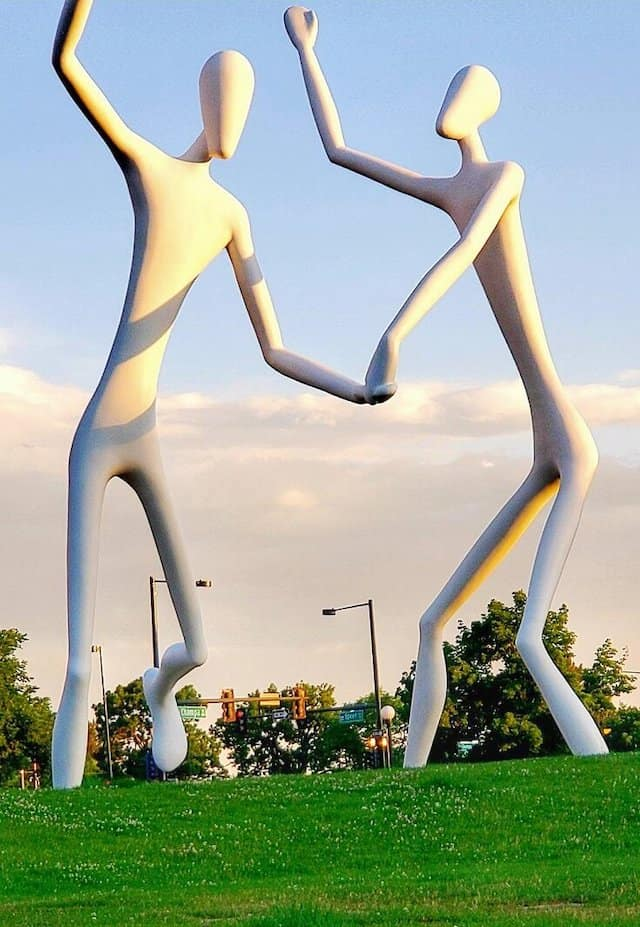 Two 60 foot high white fiberglass sculptures holding hands and dancing on a lawn