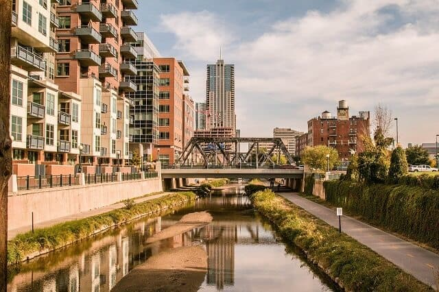 The River in Downtown Denver with a footpath running alongside the right side of the water and high rise apartments on the left with a metal industrial styled bride crossing the water