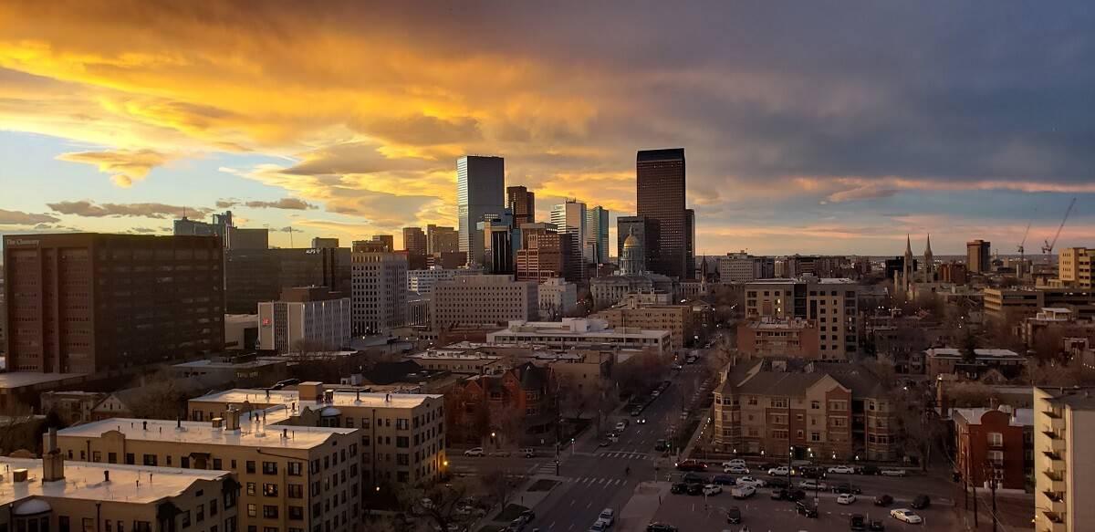 Aerial shot of Downtown Denver at sunset framed by an light orange sky - cover photo for Visiting Denver : Top Denver Travel Tips to Know Before You Go