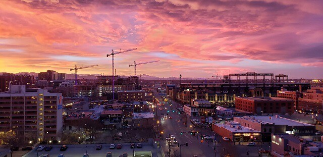 Aerial shot of Downtown Denver with several cranes rising above the buidlings and consrtuction sites at dusk with lights on in the buildings and on cars underneath a cotton candy pink sunset sky