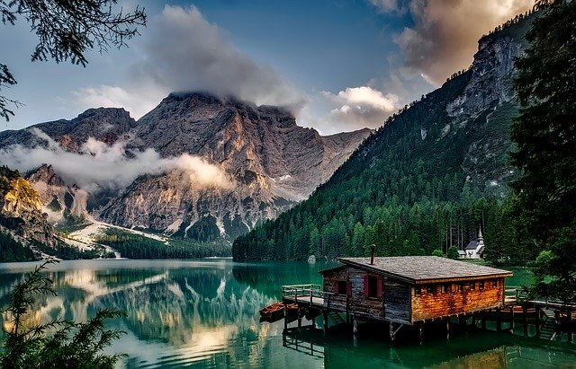 Italian lake and mountain compbination with a wooden hut in the foreground standing on stilts in the lake