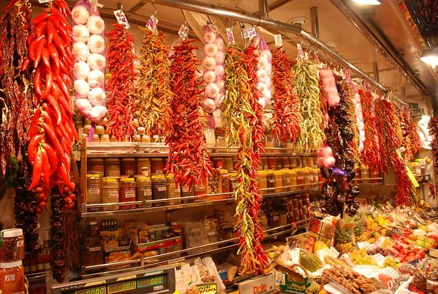 Food stall with garlic and chilli hanging from rails close to the ceiling in Barcelonas La Boqueria Market