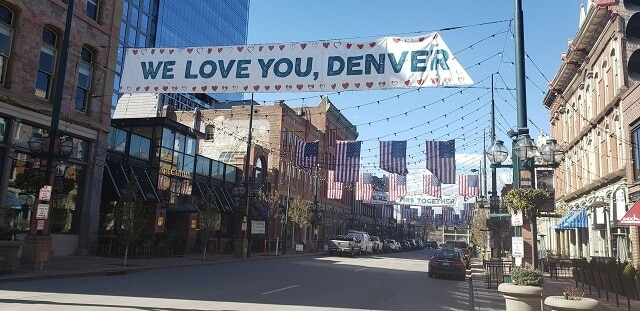 Larimer Square covered in bunting and festival lights with a banner stating 'We Love You Denver'