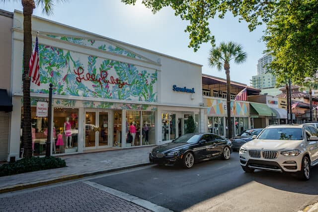 Colourful storefront on Las Olas Boulevard with a black car parked in front and palm trees on the sidewalk