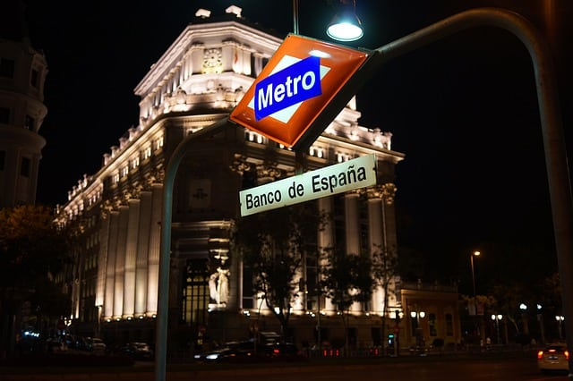 Metro Station at night in front of a white building lit up multiple uplights
