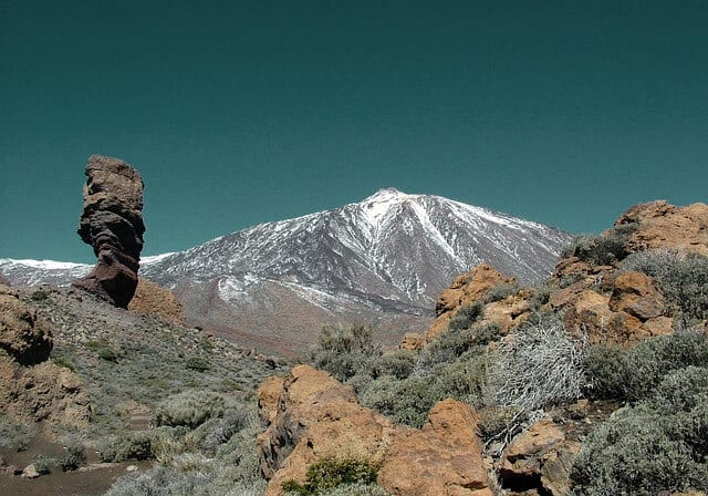 Rocky landscape looking up towards the snow covered peak of Mount Teide in Tenerife