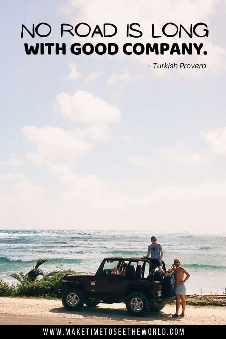 An open top jeep parked at the side of the road in front of the ocean with one guy standing in the car and one next to it with text overlay No road is long with good company