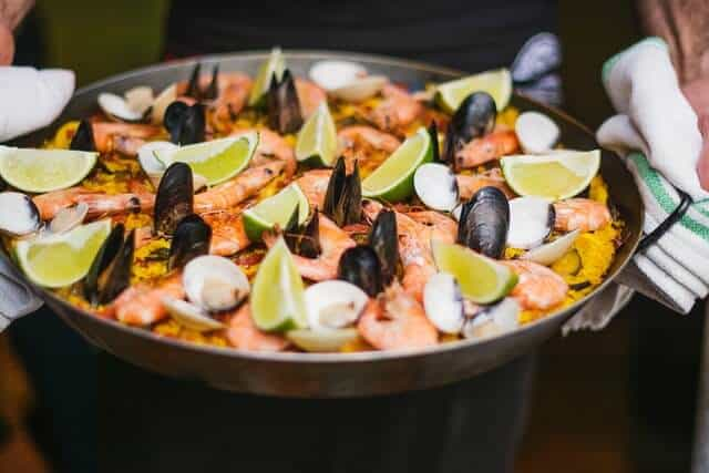 Paella pan filled with a paella topped with muscles, mushrooms, lime wedges and prawns