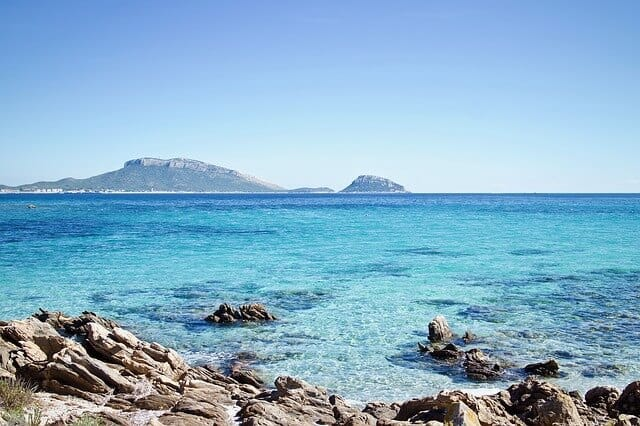 Clear blue waters of Sardina with a hilly island in the distance