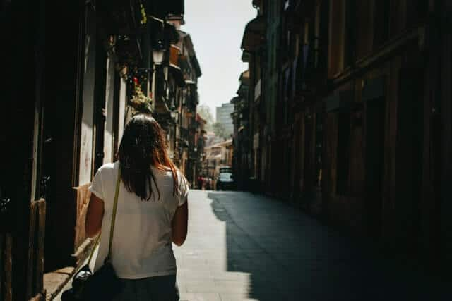 Single female traveler walking down a narrow street