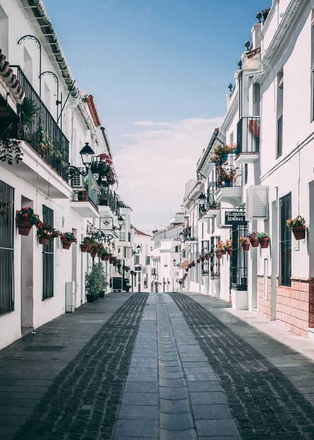 Narrow street in a spanish town with while two storey buildings lining each side of the paved central street