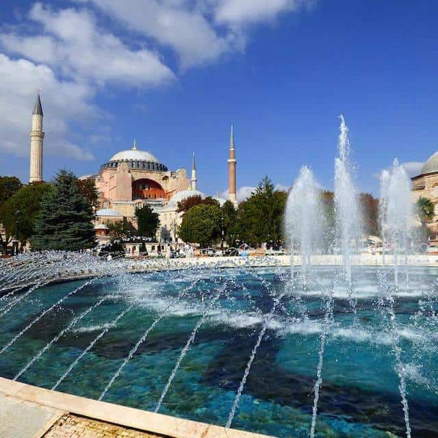 View of Sultanahmet Square in Istanbul taken from behind a fountain with the Pink Facade of the Hagia Sofia flanked by two minaret spires in the distance