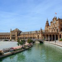 Cover photo for the Top Spain Travel Tips featuring the plaza in Seville with a palatial building standing beside a curved body of water
