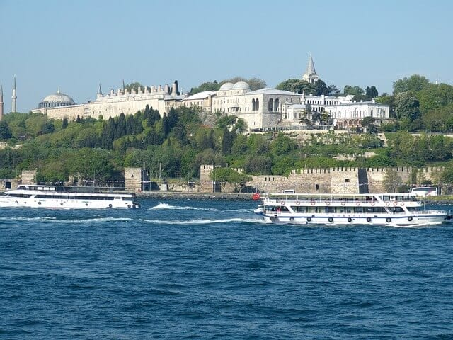 Topkapi Palace as seen from the Bosphorous River with the water in the foreground and the Palace raised up on the hill in the background