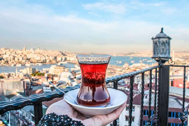 Woman holding a white plate with a tulip glass of Turkish Tea on a rooftop overlooking the Bosphoros river with the city of Istanbul in the background