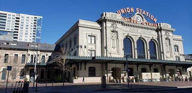 Large white building with 'Union Station Travel & Train' in giant red letters on top of the buidling under a blue sky