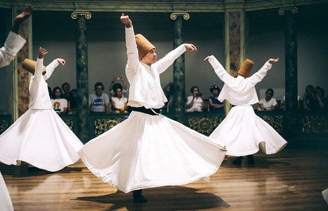 Whirling Dervish Performance featuring three Dervishes in white long skirts and tops with red fez style hats